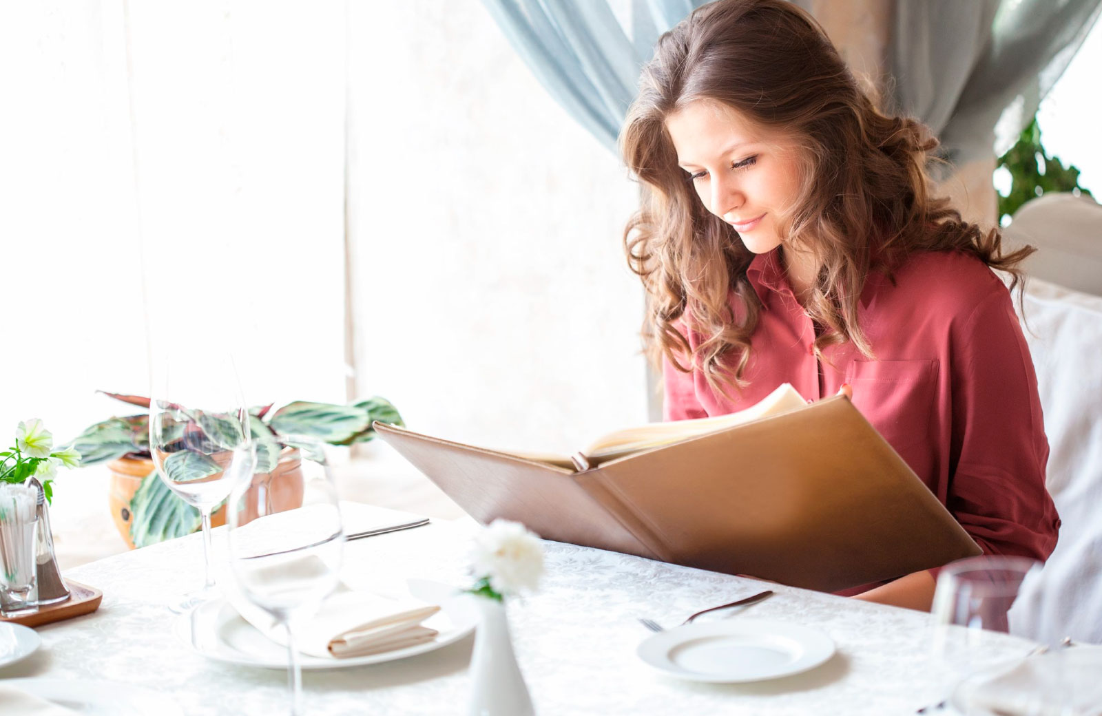 woman reading the menu in a fine dining restaurant