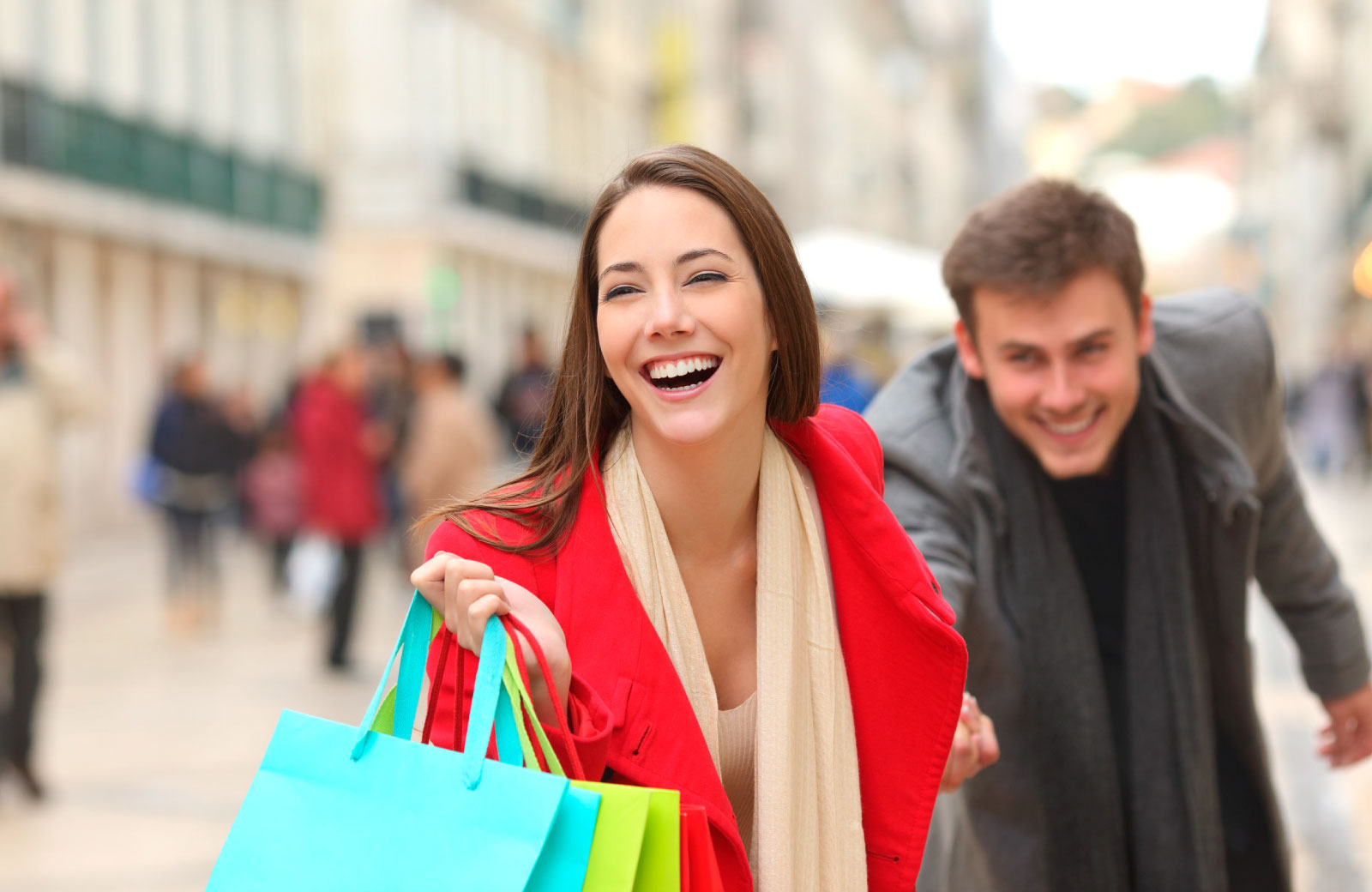 woman smiling with shopping bags and holding man's hand