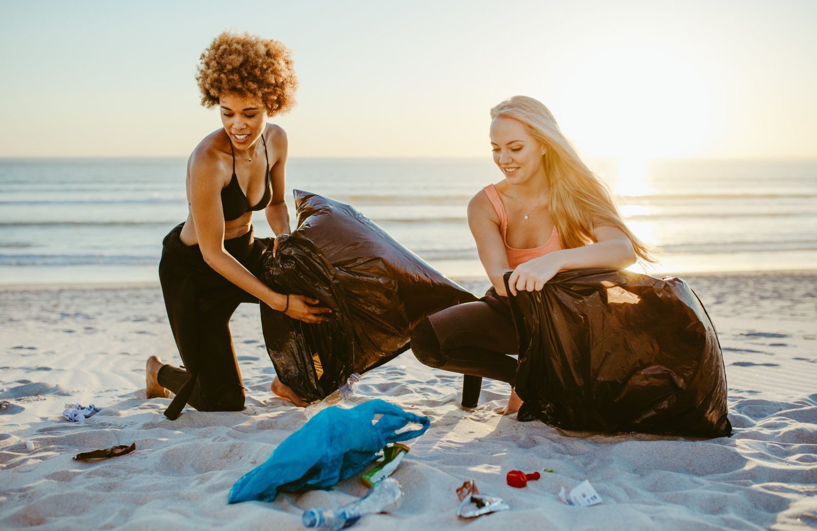 two women with garbage bags picking up trash on the beach