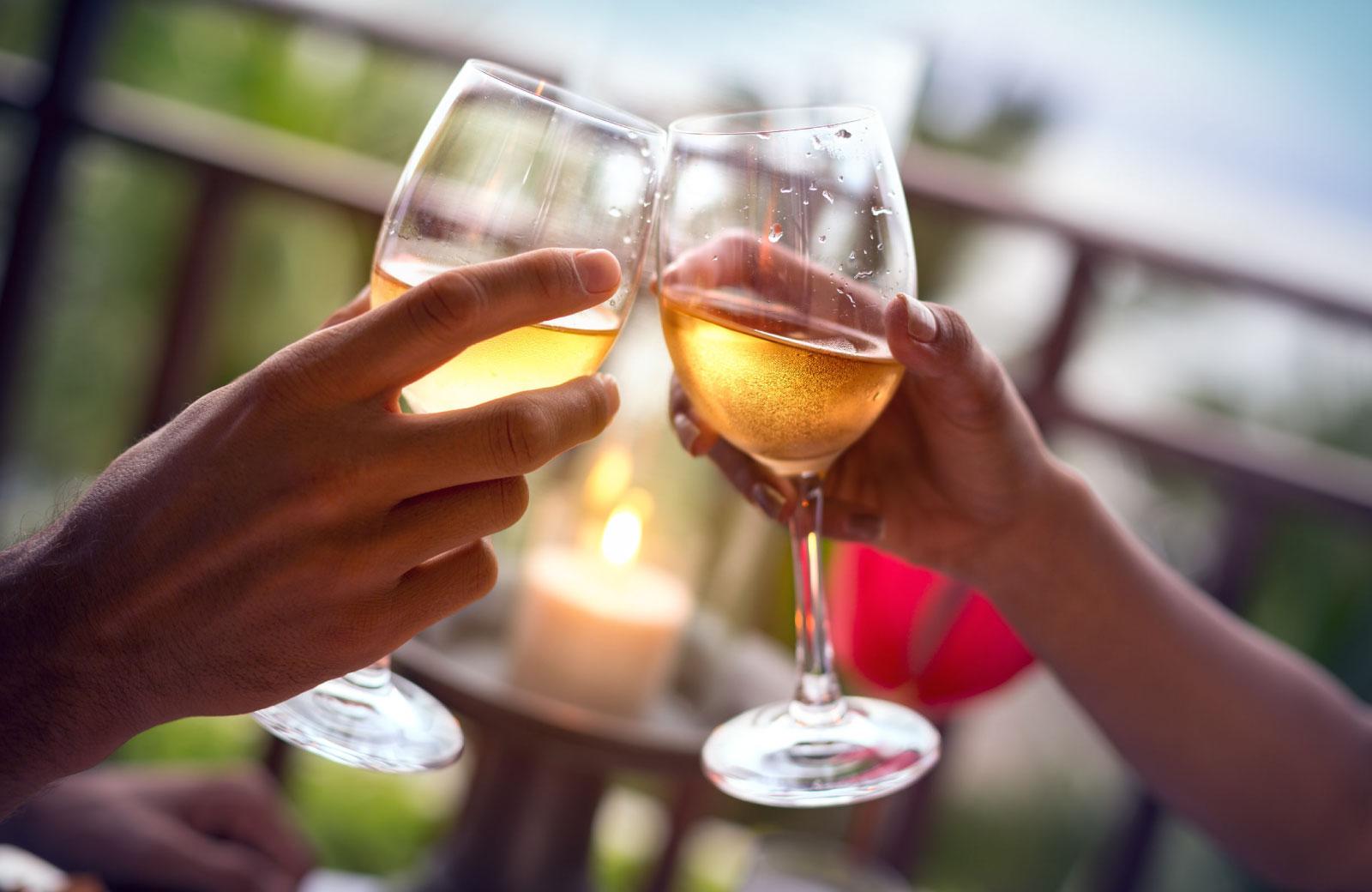 people toasting white wine in wine glasses