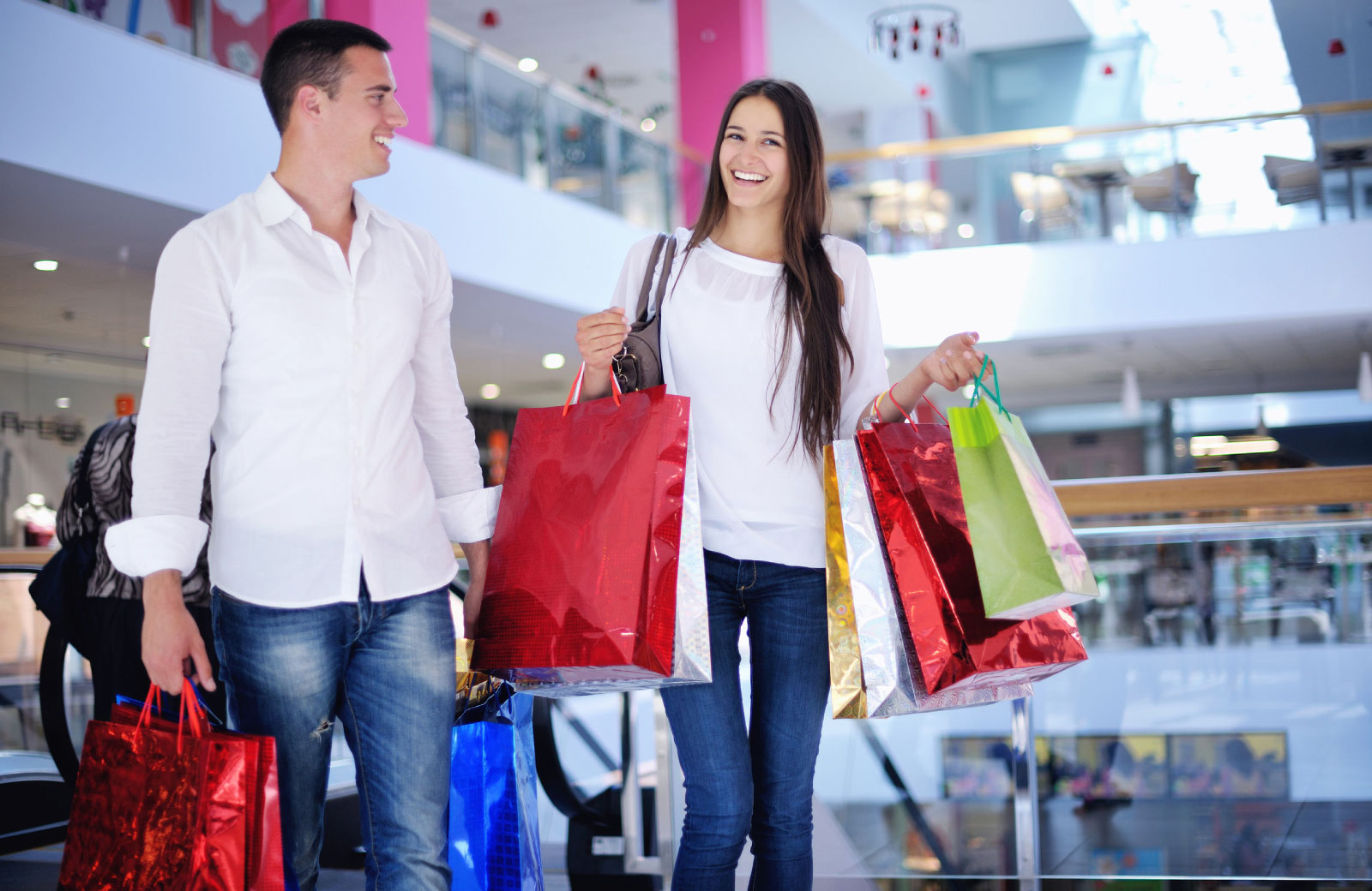 couple carrying shopping bags in a mall