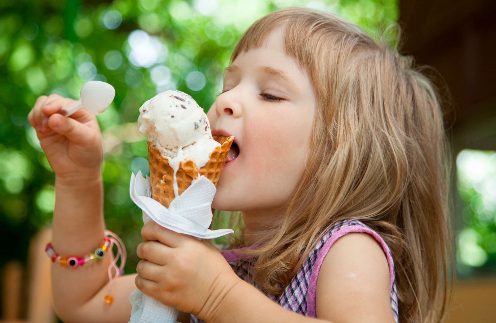 little girl eating ice cream in a cone